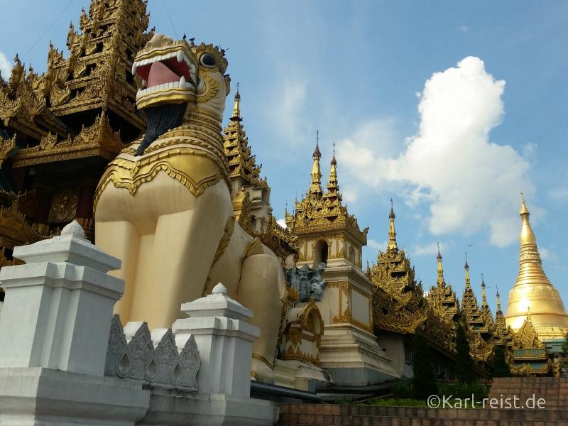 Der Haupteingang mit den dahinter liegenden, überdachten Treppen und der Shwedagon Pagode im Hintergrund.