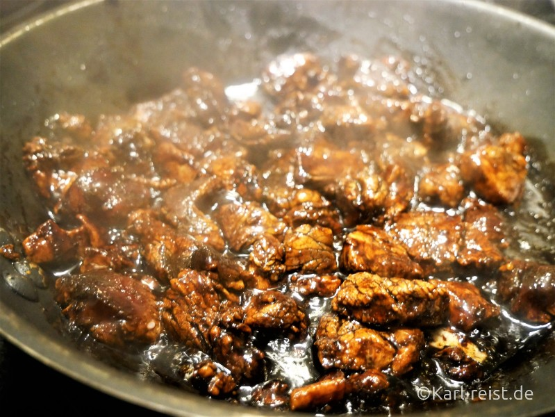 Mariniertes Fleisch in der Pfanne mit Öl und Knoblauch